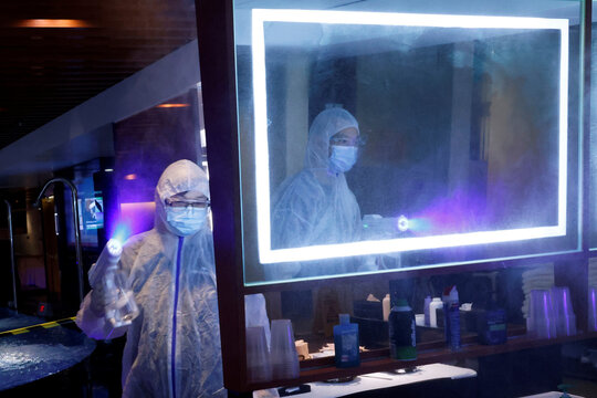 Cleaners wearing protective suits spray disinfectant at a Sauna and Spa centre to prepare the reopening, following the coronavirus disease (COVID-19) outbreak, in Hong Kong