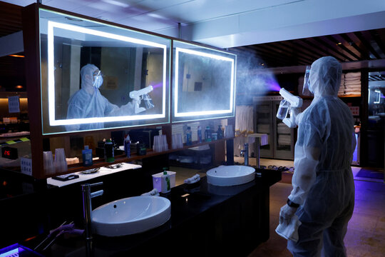 A cleaner wearing a protective suit sprays disinfectant at a Sauna and Spa centre to prepare the reopening, following the coronavirus disease (COVID-19) outbreak, in Hong Kong