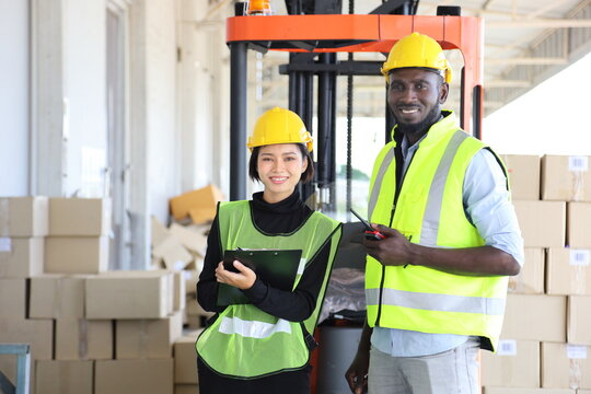 African American and Asian workers wearing safety vest while working in warehouse checking for the inventory with copy space