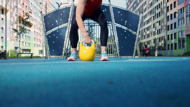 Get started. Young female athlete doing workout, training with a kettlebell in the open air.