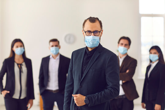 Young company leader with group of responsible workers wear face masks in their workplace