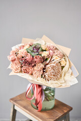 Autumn bouquet of mixed flowers with Protea and Brassica on wooden table. The work of the florist at a flower shop. Fresh cut flower.