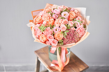 Bouquet Peach and orange color. Beautiful bunch mixed flowers in wooden table. the work of the florist at a flower shop. Fresh cut flower.