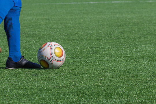 Close-up of foot of a soccer player in blue golf or leggings next to a soccer ball on a green football field