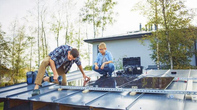 Father and Son Installing Solar Panels to a Metal Basis. They Work on a House Roof on a Sunny Day. Concept of Ecological Renewable Energy at Home and Quality Family Time.