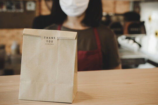 waitress wearing protection face with dessert paper set bag on counter bar waiting for customer in modern cafe coffee shop, food delivery, cafe restaurant, takeaway food, small business owner concept
