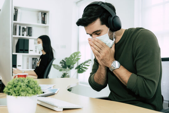 Coronavirus (COVID-19). sick young caucasian business man wearing protective face mask having cold fever and sneeze working at workplace in office, flu symptom, new normal, office syndrome concept