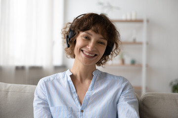 Headshot portrait of smiling young caucasian woman in headphones talk on video call from home. Profile picture of happy 40s female in headset have webcam virtual conversation or conference.