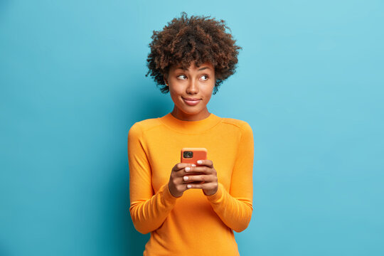 Pensive delighted young African American woman holds mobile phone and types message uses modern technologies dressed in casual jumper isolated on blue background. Teenage girl with smartphone