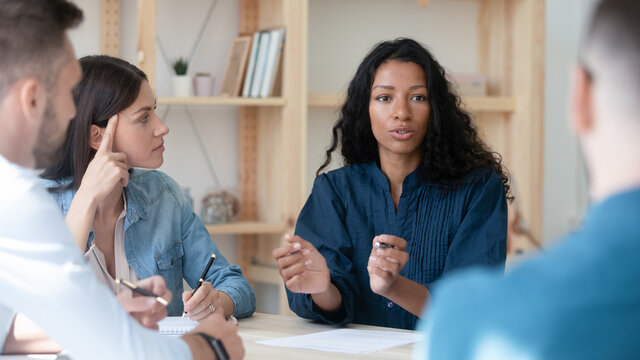 African American businesswoman mentor coach speaking, training staff at meeting, sitting at table in boardroom, female employee sharing ideas, discussing project strategy with colleagues
