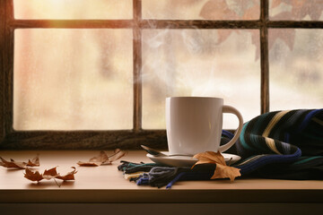 Cup in front of a window with autumn landscape