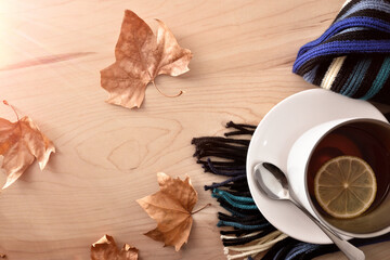 Cup with tea with lemon on  scarf on wooden table