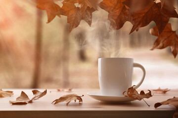Mug with hot drink on wooden table with autumn landscape