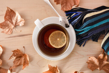 Tea with lemon on wooden table with scarf and leaves