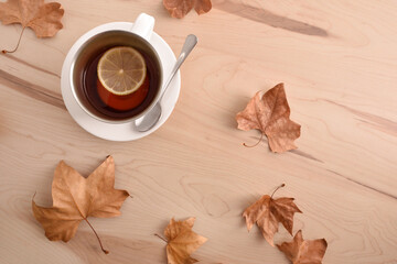 Tea with lemon on wooden table with leaves top view