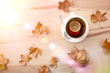 Tea with lemon on wooden table with leaves sunny top