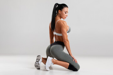 Beautiful athletic girl, sexy fitness woman in leggings on the gray background