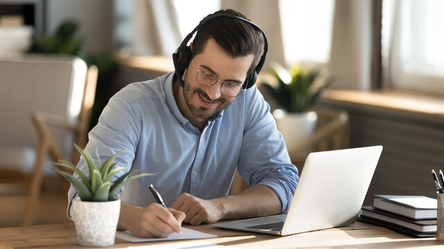 Smiling young Caucasian man in headphones glasses sit at desk work on laptop making notes. Happy millennial male in earphones watch webinar or training course or computer, study online from home.