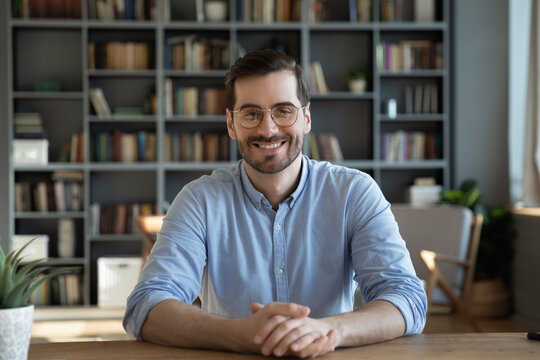 Headshot portrait of smiling 30s Caucasian millennial man in glasses sit at desk at home talk speak on video call or webcam virtual conference. Picture of happy young male in spectacles pose at table.