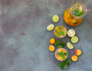 Delicious refreshing drink with apricot, lime and mint in jug and glasses on green stone...