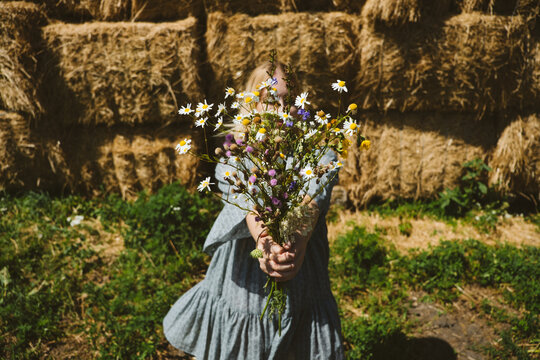 Young girl in rubber boots with flowers standing against the background of straw bales on country farm. Farming, Cottagecore, Farmcore, Countrycore aesthetics, fresh air, countryside, slow life
