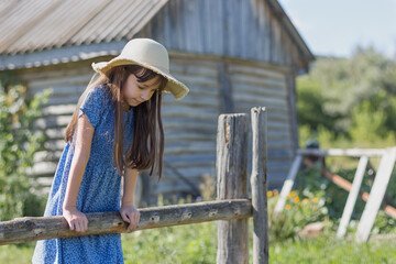 A young girl with long hair and in a hat and a dress stands near wooden fance. Portrait of cute child on a village.