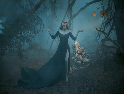 Blurred silhouette of mystical pagan woman in the fog. The witch casts a spell, prays in the forest with her hands raised to the sky against the background of a dark tree and human skulls