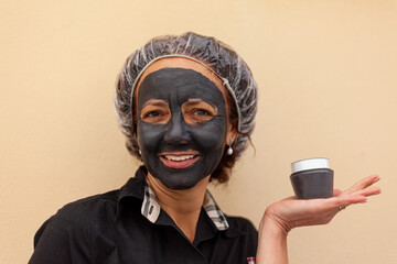 Close up of brazilian woman with mud mask holding a jar of cream.