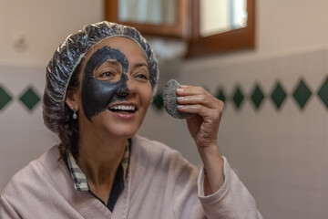 Close-up of a smiling woman while removing the mud mask from her face. Image relating to the care and beauty of the female body