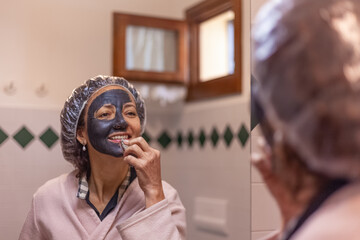 Close-up of a woman reflected on a mirror while removing the mud mask from her face. Image relating to the care and beauty of the female body