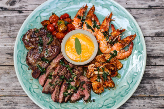 Surf and turf serving seafood and grilled ribeye steak platter.