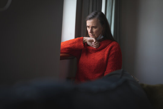 Stresses woman sitting besides the window at home