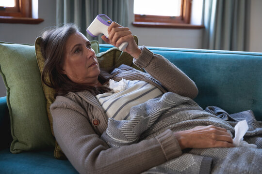 Sick woman measuring her temperature using temperature gun while laying on the couch