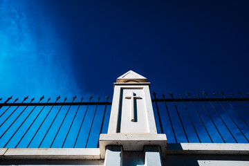 High white concrete walls with metal bars separate the dead from an outside cemetery, background with a blue sky.
