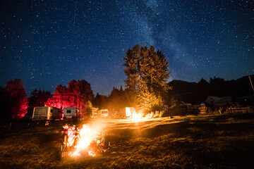 Group of friends chill and warm near a bonfire in camping during a hiking trip