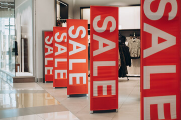 Red banners SALE on anti-thieft gate sensor at clothing store entrance. Black friday sale and seasonal discounts