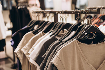 Hanger with women's t-shirts in casual store. Monochrome colors. Selective focus