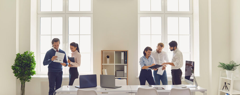 Happy company workers meeting, talking, discussing business projects in modern office workspace