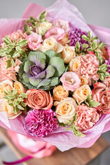 Beautiful spring bouquet on wooden table.. Arrangement with various flowers. The concept of a flower shop. A set of photos for a site or catalogue. Work florist.