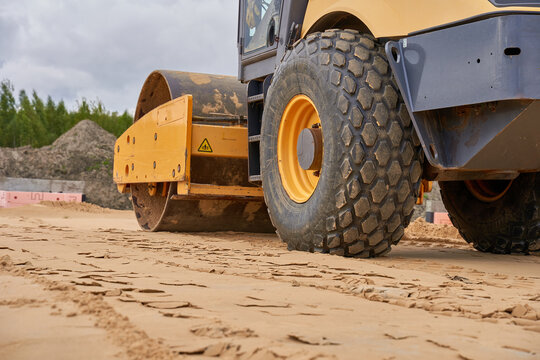 a huge yellow roller dozer compacts the soil to prepare the foundation at the construction site