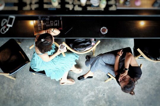 Aerial view couple of women sit and talk in the coffee shop. Lifestyle and friendship