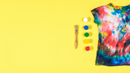 Tie dye t-shirt with scattered colors on a yellow background. Flat lay. Place for text. Fotobehang