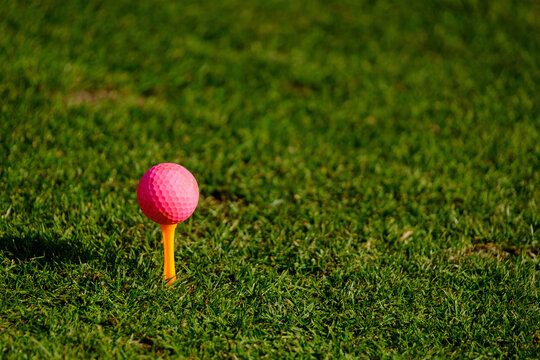 close-up of pink golf ball on yellow tee on golf course