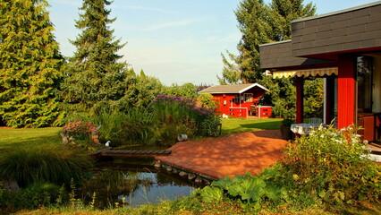 moderner Bungalow mit malerischem Garten, Teich und Terrasse an sonnigem Herbsttag