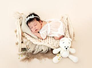 Nice newborn sleeping on small bed