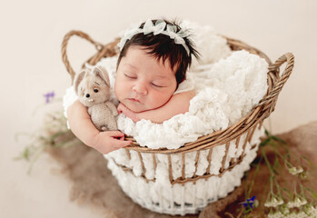 Funny newborn in basket on stomach