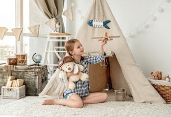 Happy little girl flying wooden plane