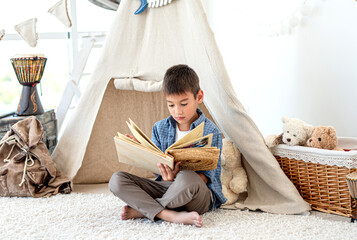 Little boy reading paper book in room