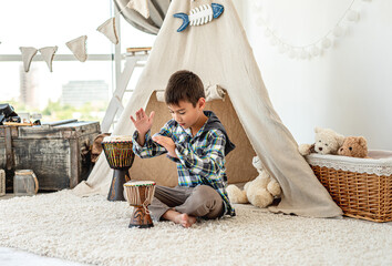 Little boy playing djembe drums indoors