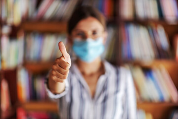 Closeup of college girl standing in library and holding thumbs up. She is having face mask to prevent corona virus from spreading.